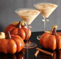 Two Orange looking martinis next to pumpkins